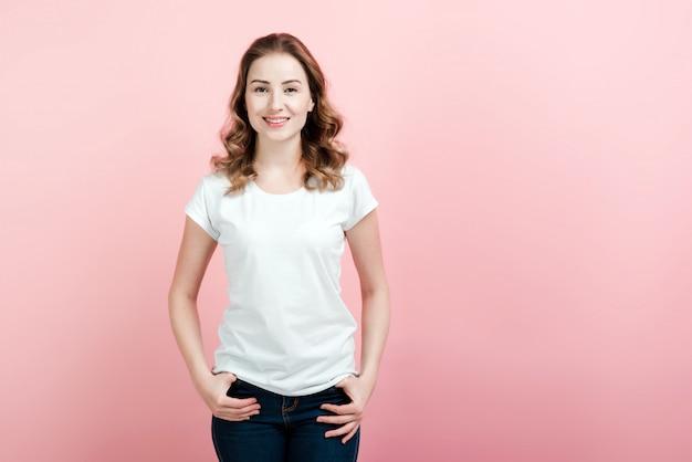 Jonge, mooie vrouw in witte t-shirt en spijkerbroek poseren