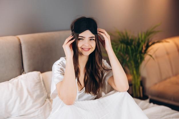 Jonge mooie vrouw in witte zijden pyjama met een zwart slaapmasker op haar hoofd. een brunette met een slaapmasker op haar hoofd zit op een bed en lacht. ochtend of avond in het bed in de slaapkamer.