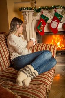 Jonge mooie vrouw in wollen sokken ontspannen op de bank bij de brandende open haard en het drinken van thee