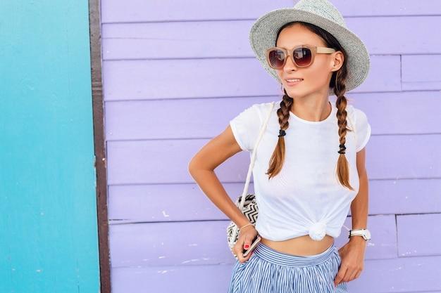 Jonge mooie vrouw in zomer mode-outfit, casual stijl, poseren tegen kleurrijke muur, reizen, hoed, zonnebril, glimlachen, gelukkig