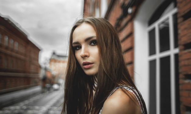 Jonge mooie vrouw in zomerjurk op straat op stad