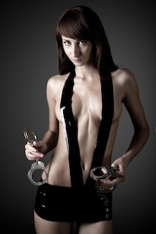 Jonge mooie vrouw in zwart leer sexy kostuum die zich met handboeien over grijze achtergrond bevinden. schoonheid van het lichaam van de vrouw, seks, bdsm concept