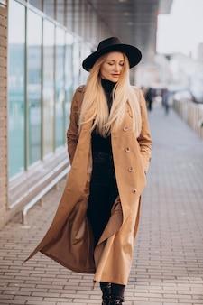 Jonge mooie vrouw in zwarte hoed en beige jas wandelen door winkelcentrum