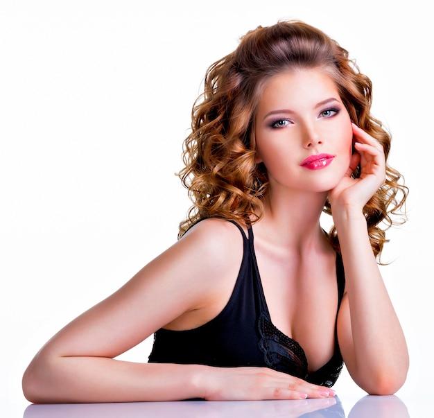Jonge mooie vrouw in zwarte jurk camera kijken