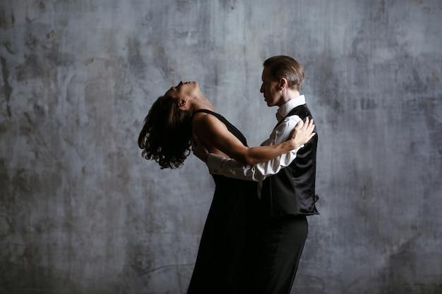 Jonge mooie vrouw in zwarte jurk en man tango dansen