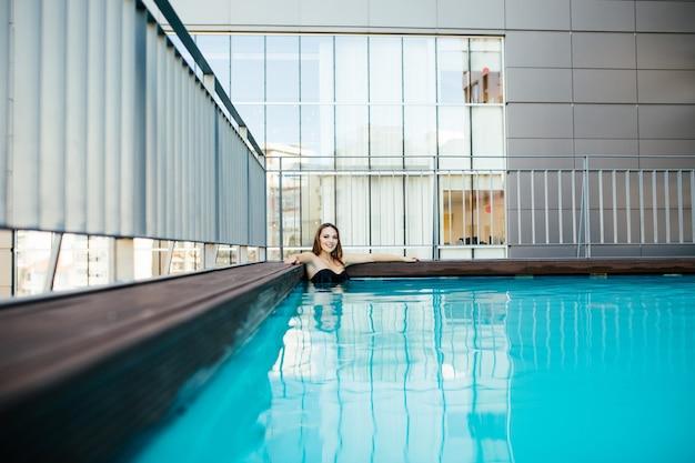Jonge mooie vrouw in zwarte zwembroek ontspant aan de rand van het zwembad