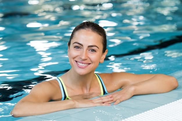 Jonge mooie vrouw in zwembad