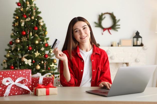 Jonge mooie vrouw is thuis aan het winkelen voor kerst in een feestelijk interieur
