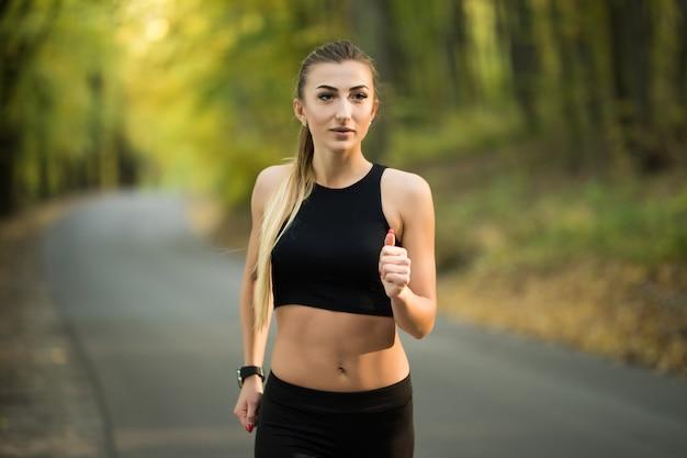 Jonge mooie vrouw joggen in het park in de zomer