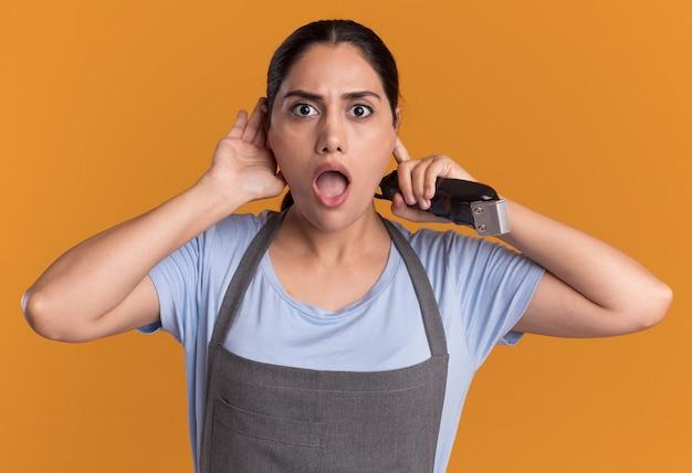 Jonge mooie vrouw kapper in schort bedrijf trimmer bedrijf hand over haar oor kijken verrast staande over oranje muur