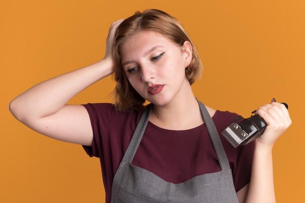 Jonge mooie vrouw kapper in schort bedrijf trimmer opzij kijken met peinzende uitdrukking denken staande over oranje muur