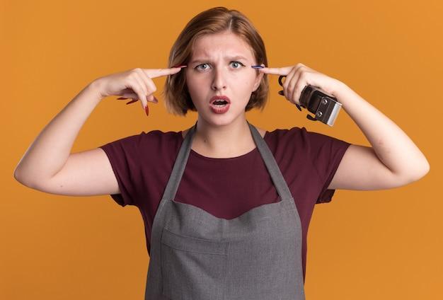 Jonge mooie vrouw kapper in schort bedrijf trimmer wijzend op haar tempels kijken verward staande over oranje muur