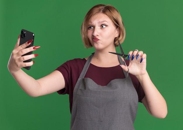 Jonge mooie vrouw kapper in schort met behulp van smartphone selfie doen met een schaar wordt verward staande over groene muur