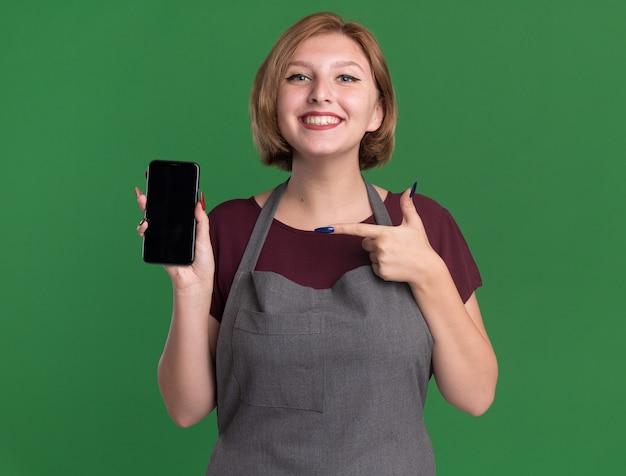 Jonge mooie vrouw kapper in schort met smartphone wijzend met wijsvinger naar het glimlachend vrolijk staande over groene muur