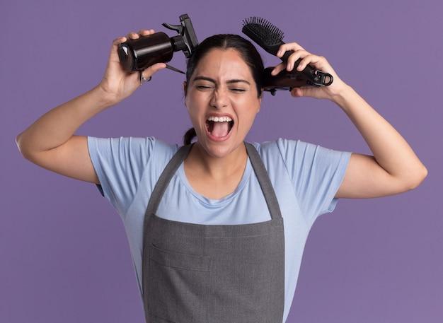 Jonge mooie vrouw kapper in schort met spuitfles trimmer machine en haar schreeuwen met geïrriteerde uitdrukking borstel staande over paarse muur