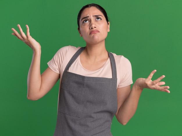 Jonge mooie vrouw kapper in schort opzoeken verward met opgeheven armen staande over groene muur