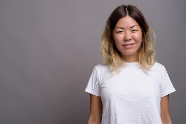Jonge mooie vrouw kazachse tegen grijze muur