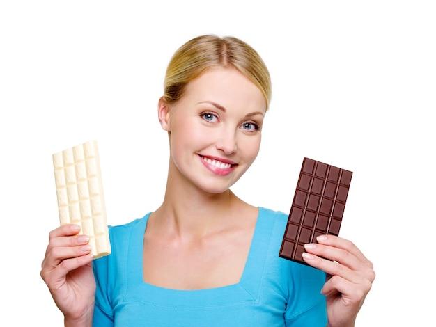 Jonge mooie vrouw kiezen uit zoete en bittere chocolade - op een witte