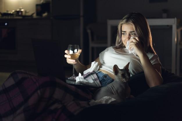 Jonge mooie vrouw kijken naar film thuis 's nachts