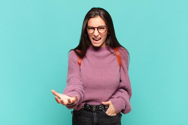 Jonge mooie vrouw kijkt boos, geïrriteerd en gefrustreerd schreeuwend wtf of wat is er mis met je. studentenconcept