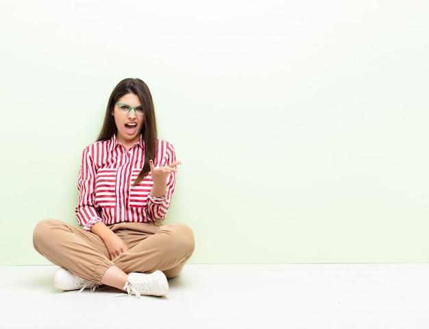 Jonge mooie vrouw kijkt boos, geïrriteerd en gefrustreerd schreeuwend wtf of wat is er mis met jou zittend op de vloer