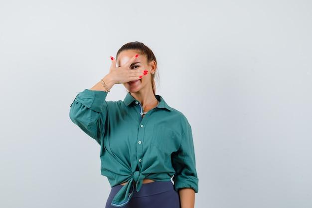 Jonge mooie vrouw kijkt door vingers in groen shirt en ziet er vrolijk uit. vooraanzicht.