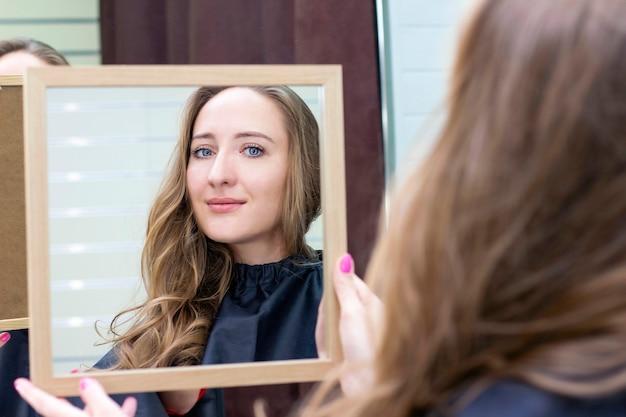 Jonge mooie vrouw kijkt in de spiegel in een schoonheidssalon. make-up en kapsel