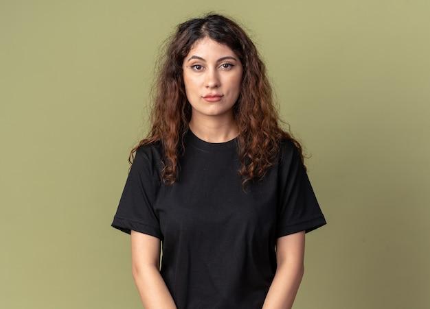 Jonge mooie vrouw kijkt naar de voorkant geïsoleerd op olijfgroene muur met kopieerruimte