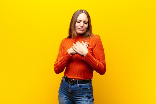 Jonge mooie vrouw kijkt verdrietig, gekwetst en diepbedroefd, houdt beide handen dicht bij het hart, huilt en voelt zich depressief over de oranje muur