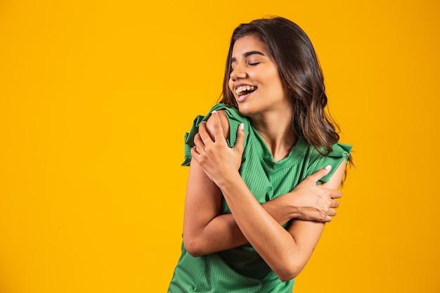 Jonge mooie vrouw knuffelen zichzelf gelukkig en positief, glimlachend zelfverzekerd. zelfliefde en zelfzorg