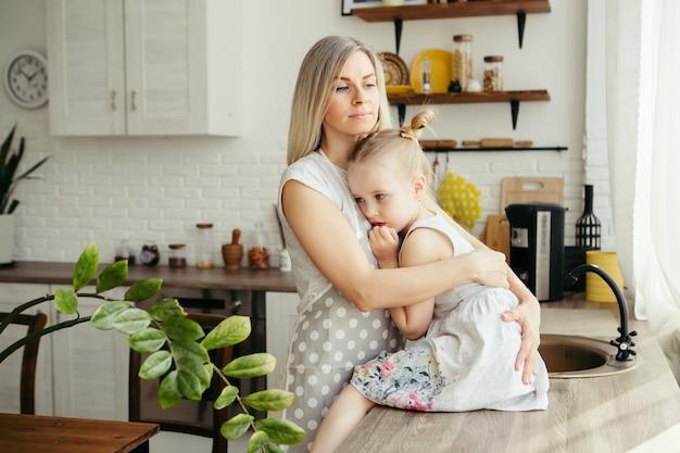 Jonge mooie vrouw knuffelt en kust haar schattige dochtertje. tonen.