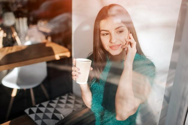 Jonge mooie vrouw koffie drinken in café-bar