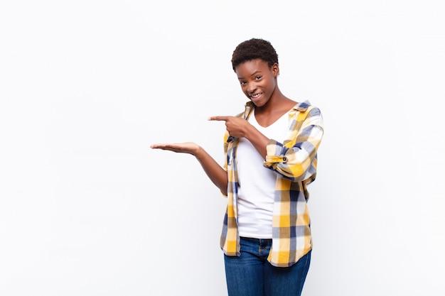 Jonge mooie vrouw lachend vrolijk en wijzend naar de ruimte op de palm aan de zijkant te kopiëren, een object te tonen of te adverteren