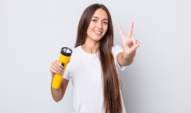 Jonge mooie vrouw lacht en ziet er gelukkig uit, gebarend overwinning of vrede. lantaarn concept