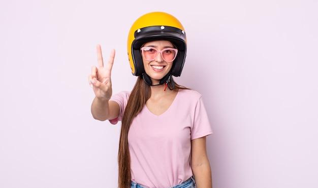 Jonge mooie vrouw lacht en ziet er gelukkig uit, gebarend overwinning of vrede. motorrijder en helm