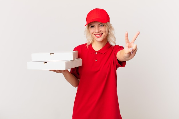Jonge mooie vrouw lacht en ziet er gelukkig uit, gebarend overwinning of vrede. pizza bezorgconcept