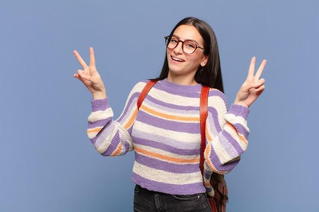Jonge mooie vrouw lacht en ziet er gelukkig, vriendelijk en tevreden uit, gebarend overwinning of vrede met beide handen. studentenconcept