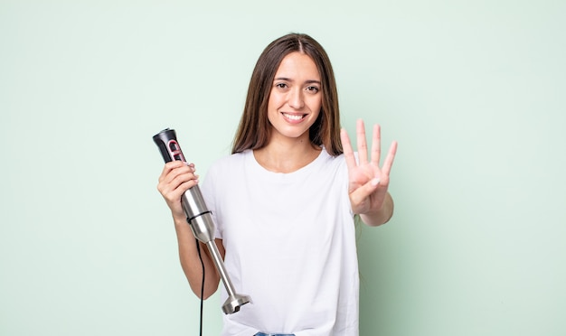 Jonge mooie vrouw lacht en ziet er vriendelijk uit, met nummer vier. handmixer concept