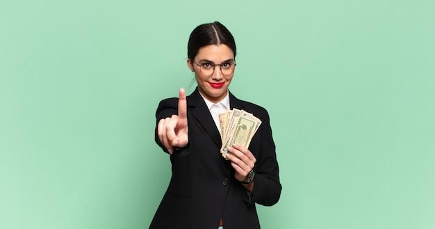 Jonge mooie vrouw lacht en ziet er vriendelijk uit, nummer één of eerst met de hand naar voren, aftellend. bedrijfs- en bankbiljettenconcept