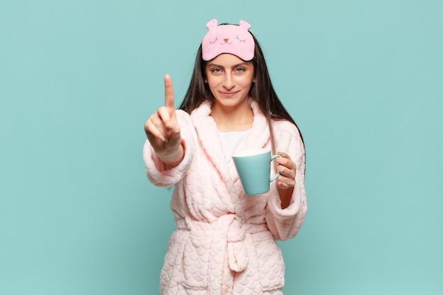 Jonge mooie vrouw lacht en ziet er vriendelijk uit, nummer één of eerst met de hand naar voren, aftellend. wakker worden met pyjama's concept