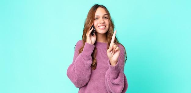 Jonge mooie vrouw lacht en ziet er vriendelijk uit, toont nummer één en gebruikt een smartphone