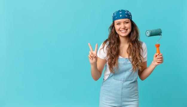 Jonge mooie vrouw lacht en ziet er vriendelijk uit, toont nummer twee en schildert een muur