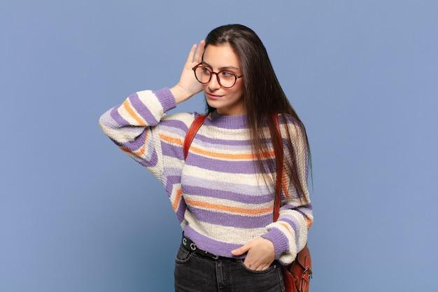 Jonge mooie vrouw lacht, kijkt nieuwsgierig naar de zijkant, probeert te luisteren naar roddels of een geheim af te luisteren. studentenconcept