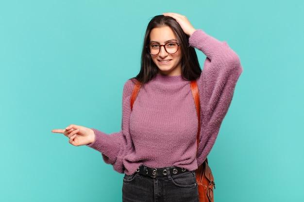 Jonge mooie vrouw lacht, ziet er gelukkig, positief en verrast uit en realiseert zich een geweldig idee dat naar de laterale kopieerruimte wijst. studentenconcept