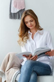 Jonge mooie vrouw leest een tijdschrift, zittend in een stoel in een gezellige lichte woonkamer