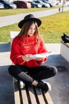 Jonge mooie vrouw legt op groen veld en leest boek.