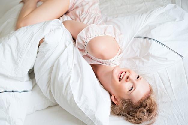 Jonge mooie vrouw leuke ochtend wakker in bed, witte slaapkamer