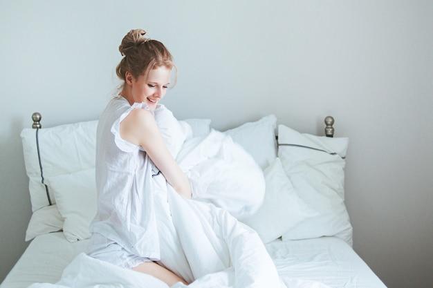 Jonge mooie vrouw leuke ochtend wakker in bed