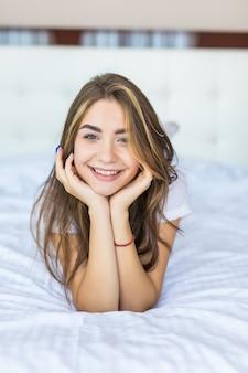 Jonge mooie vrouw liggend aan het einde van het bed glimlachend met haar hoofd op haar hand rustend.