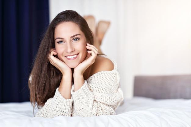 Jonge mooie vrouw liggend op bed in de ochtend